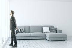 Man in modern living room. Handsome european businessman looking out of window in modern living room interior with sofa, copy space on concrete wall and city Royalty Free Stock Images