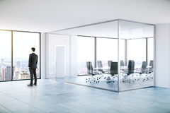 Man in modern meeting room. Businessman looking out of window in modern meeting room with panoramic city view. 3D Rendering royalty free stock images