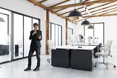 Man in modern office interior. Businessman standing in modern coworking office interior with city view. Design and style concept. 3D Rendering Royalty Free Stock Images