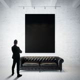 Man in modern suit looking at black poster holding on the white brick wall. Classic sofa, wood floor. Vertical Royalty Free Stock Photos