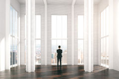 Man in modern sunny loft design room with city view Royalty Free Stock Photo