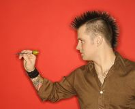 Man with mohawk throwing dart. Stock Images