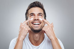 Man with moisturizer on the face Stock Photography