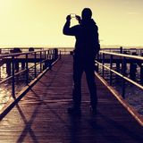 Man on mole takes pictures of spring  morning at sea Royalty Free Stock Photos