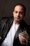 Man With Money. A middle aged man wearing a leather jacket holding a handful of one hundred dollar bills. Shallow depth of field Stock Photography
