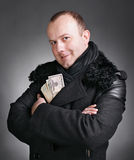 Man with money. Young handsome man in winter coat with money on a gray background stock photography