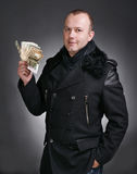 Man with money. Young handsome man in winter coat with money on a gray background royalty free stock image