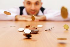 Man and money. Man is looking at falling coins royalty free stock photography