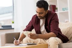 Man with money and calculator filling papers. Business, finances, accounting and people concept - man with money and calculator filling papers at home Royalty Free Stock Photos
