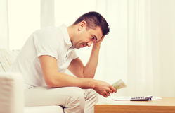 Man with money and calculator at home Stock Image