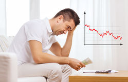 Man with money and calculator at home Royalty Free Stock Photography
