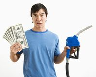 Man with money and gas nozzle. Royalty Free Stock Photos