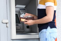 Man with money near cash machine outdoors. Closeup stock photography
