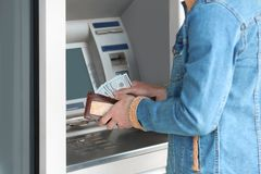 Man with money near cash machine outdoors. Closeup royalty free stock photos