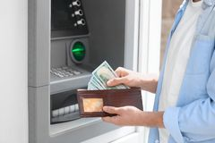 Man with money near cash machine outdoors. Closeup stock images
