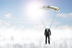 Man with money parachute flying in the sky Royalty Free Stock Photos