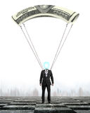 Man with money parachute landing on chessboard ground Royalty Free Stock Photography