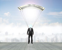 Man with money parachute landing on wooden floor Stock Photography