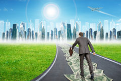 Man on money road leading to city Royalty Free Stock Photo