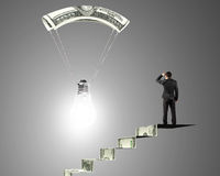 Man on money stairs looking light bulb with money parachute Stock Images