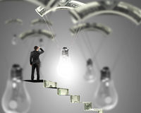 Man on money stairs looking light bulb with money parachute Royalty Free Stock Images