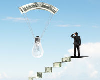 Man on money stairs looking light bulb with money parachute Royalty Free Stock Photos
