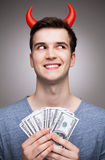 Man with money wearing devil horns