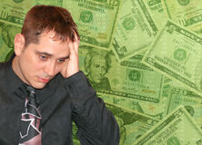 Man with Money Worries. A business man is has his hand to his forehead and is worried. Money is in the background Stock Image