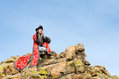 Man in Mongolian costume on rock Royalty Free Stock Photos