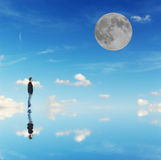 Man and moon. Man looking at the moon in a blue background Stock Image