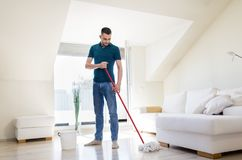 Man with mop and bucket cleaning floor at home Royalty Free Stock Photos
