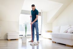Man with mop and bucket cleaning floor at home Stock Images