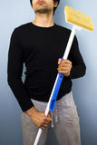 Man with mop. Young multiracial man holding a mop Stock Image