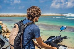 A man on a moped, motorbike admires the beautiful sea.  royalty free stock photos
