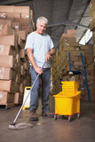 Man moping warehouse floor Royalty Free Stock Photography