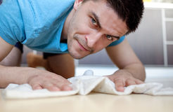 Man mopping the floor. Man in blue tee manually mopping the tile floor in his house Stock Image