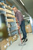 Man mopping floor warehouse. Man mopping floor of warehouse Stock Photography