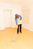 Man mopping floor. Young african man mopping the floor in his empty apartment Stock Photo