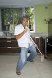 Man mopping the kitchen floor. Royalty Free Stock Images