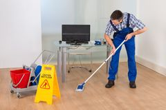 Man mopping office with wet floor sign. Portrait Of A Male Janitor Cleaning Office With Wet Floor Sign Stock Photo