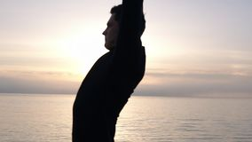A man in morning dusk warms up during an early morning workout engaged in sport. Caucasian man exercising, stretches his. Hands and fists on the wooden stock video