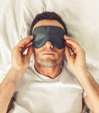 Man in the morning. Portrait of handsome man in sleeping mask lying in bed Stock Photo