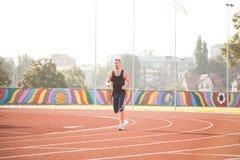 A man on a morning run in the stadium stock photo