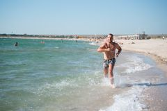 Man in motion of running on beach. Front view of sportive man running fast alongside water on beach in bright sunlight Royalty Free Stock Image