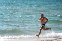 Man in motion of running on beach. Side view of sportive man running fast alongside water on beach in bright sunlight Royalty Free Stock Photography