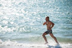 Man in motion of running on beach. Side view of sportive man running fast alongside water on beach in bright sunlight Royalty Free Stock Photos