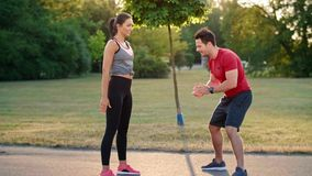 Man motivating her girlfriend during training. Outdoors stock footage