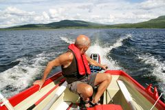 Man in a motor boat. Senior in a motor boat on a lake in Norway Stock Photos