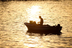 Man in motor boat at sunset Royalty Free Stock Image