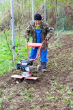 Man with motor cultivator against spring time Royalty Free Stock Images